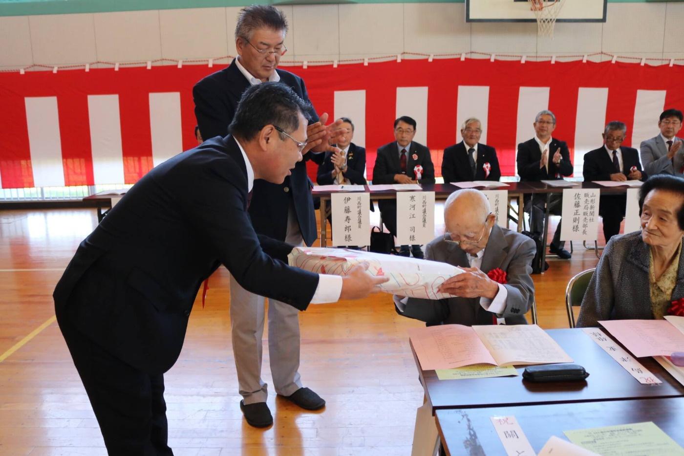 川西町と地区社協推進委員会からの記念品が贈呈されている様子