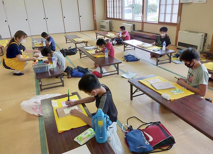 写真:第3回わんぱくキッズスクール:筆ペン絵文字教室に参加している児童