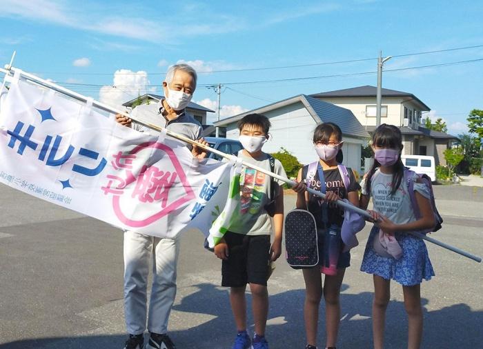 写真:キラリかけ愛運動の旗を持った小学生と(特)きらりよしじまネットワーク理事長